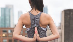 A woman practices yoga with a city in the backdrop, representing the practice of slowing your heart rate.