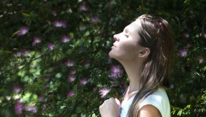 A woman taking a depth breath used to represent breathing exercises.
