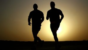 Two men are seen running with the sun setting behind them.