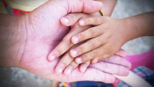 A closeup on an adult hand holding a child's hands.
