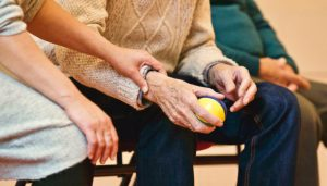 A woman from a Holistic Care team holds a senior's wrist in comfort.