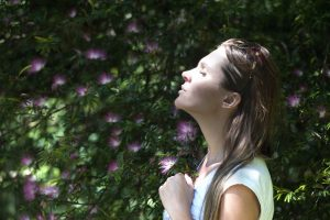 A woman inhales with flowers in the background.