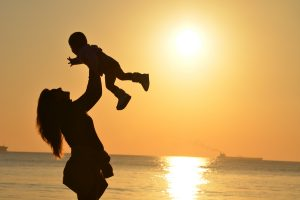 A woman holds her newborn in the air as the sun sets near the beach.
