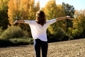 A woman standing straight up, arms open wide, surrounded by nature and fall colors.