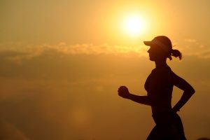 Silhouette of a woman running with a sunset in the background.
