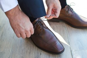 A man finishing tying his dress shoes.