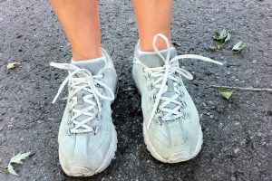 A woman poses in worn out running shoes.