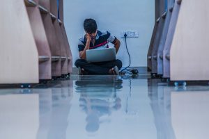 A teenager sits on the floor, against a wall, hunched over his laptop.