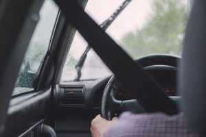 A driver is seen braving rainy conditions on the road in his vehicle.